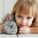 girl-lying-on-white-surface-petting-gray-rabbit-1462634